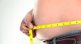 Obese person measuring his belly.