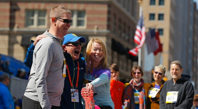 2013 Boston Marathon bombing survivor Adrianne Haslet-Davis (3rd L) and her husband Adam Davis (L) pose for a photograph after crossing the marathon finish line during a Tribute Run for survivors and first responders in Boston, Massachusetts April 19, 2014. The 118th running of the Boston Marathon will be held on April 21.  REUTERS/Brian Snyder (UNITED STATES - Tags: SPORT ATHLETICS) - RTR3LWXN