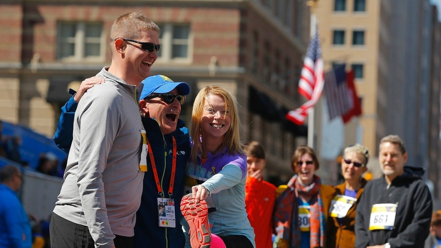 2013 Boston Marathon bombing survivor Adrianne Haslet-Davis (3rd L) and her husband Adam Davis (L) pose for a photograph after crossing the marathon finish line during a Tribute Run for survivors and first responders in Boston, Massachusetts April 19, 2014.