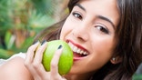Young woman face eating a green apple and looking at the camera with a smile