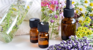 essential oils and natural cosmetics with fresh herbal leaves and flowers for beauty treatment
