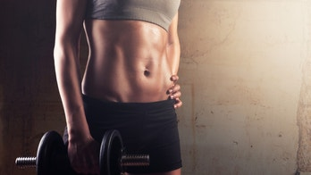 Sporty athletic woman holding dumbbell