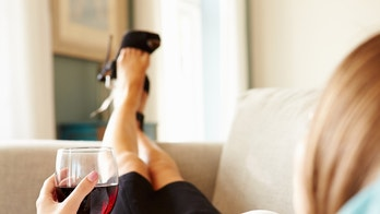 Woman Relaxing On Sofa With Glass Of Wine After Work