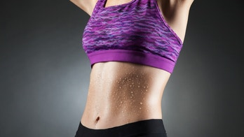 Fit anonymous sport-girl in black yoga pants and purple top with heat droppings on abdominal muscles. Studio portrait black background.