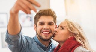 Cheerful loving couple is making selfie on smartphone. Man is looking at camera and smiling. Woman is kissing him with love