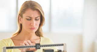 Young Caucasian woman using balance weight scale at gym