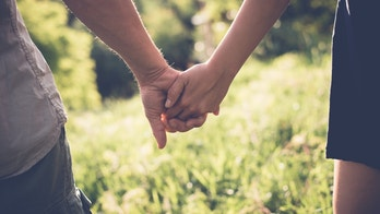 Young couple in love walking in the summer park holding hands, filtered image