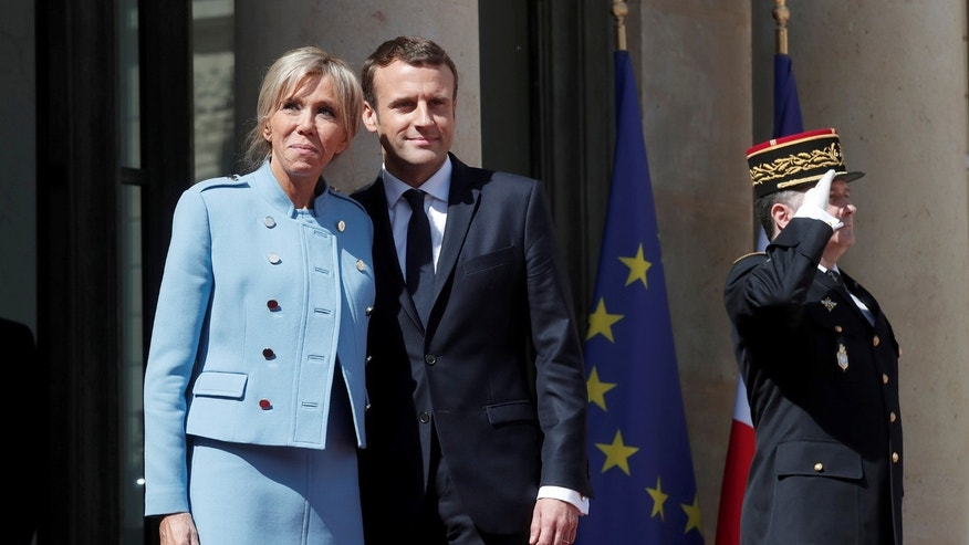 French President Emmanuel Macron and his wife Brigitte Trogneux stand on the steps of the Elysee Palace after the handover ceremony in Paris, France, May 14, 2017.
