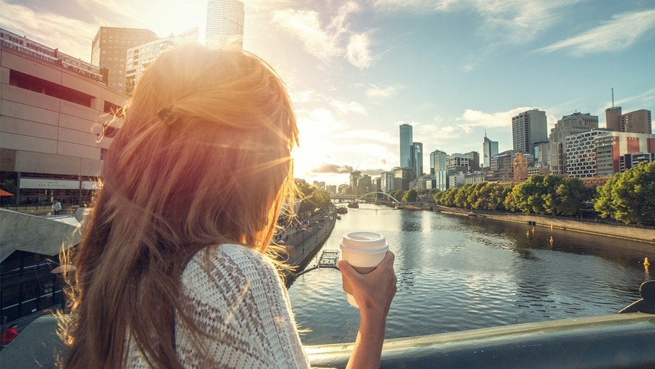 A woman enjoys the sunrise in Melbourne, Australia.