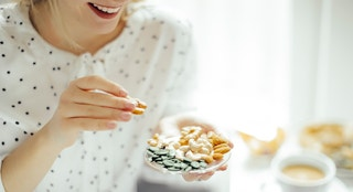 woman eating nuts istock
