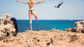 Natural beautiful Woman throwing away her clothes jumping of a cliff in to the ocean.