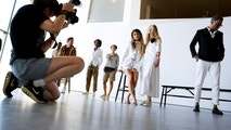 A woman takes a photograph as models pose during a presentation of the J. Crew Spring/Summer 2017 collection during New York Fashion Week in the Manhattan borough of New York, U.S., September 11, 2016.  REUTERS/Lucas Jackson  - S1BEUASYLUAA