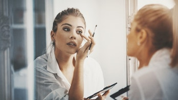 Closeup of attractive mid 20's blond woman putting on some makeup in front of large bathroom mirror. Shot from behind, focus is on her reflection. Softly toned and desaturated.