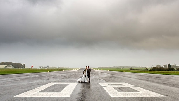 PIC BY Capture Every Moment Photography / CATERS NEWS -(PICTURED a couple on the runway PIC TAKEN 24/10/17 ) Couples with a head for heights can now get married on the worlds first licensed Boeing 747 party plane. Cotswold Airport, near Gloucestershire, has been given a licence to perform civil wedding ceremonies and naming ceremonies aboard its Boeing 747 plane and in their operational control tower  the only such venues in the world. The unique plush plane will see brides walking down a very different kind of aisle as they prepare to exchange vows in the huge commercial airliner. The aircraft took seven months to transform and despite some of the original decor, including the seating numbers still being visible, the plane can be styled in lots of different ways just like a normal wedding venue. Because of the vast space on-board, staff can also set up stages, makeup rooms and dressing rooms, all separate from the main area. SEE CATERS COPY