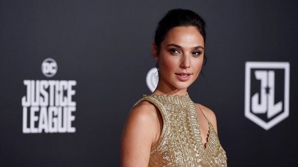 "FILE - In this Nov. 13, 2017 file photo, Gal Gadot, a cast member in ""Justice League,"" poses at the premiere of the film at the Dolby Theatre in Los Angeles. Gadot, Halle Berry and Chris Hemsworth were among the first presenters announced, Thursday, Dec. 28 for next month's Golden Globe Awards. The 75th Golden Globe ceremony will air Jan. 7, 2018.  (Photo by Chris Pizzello/Invision/AP, File)"