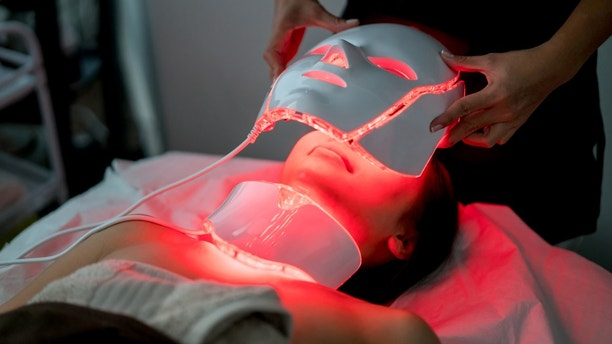 Woman at the spa getting skin laser treatment on her face - beauty concepts