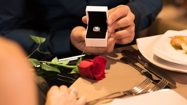 Young man presenting engagement ring to girlfriend. Husband gifting a diamond ring to wife on anniversary. Man holding box with ring making propose to girlfriend.