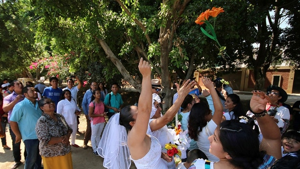 Women throw a bouquet of flowers during a wedding between people and trees to raise awareness and respect to trees and to stop illegal logging in San Jacinto Amilpas, Oaxaca state, Mexico February 25, 2018. REUTERS/Jorge Luis Plata NO RESALES. NO ARCHIVES - RC1BF6435830