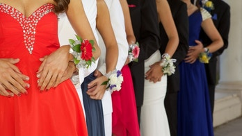 A large group of teenagers ready for the prom standing in a line. The focus is on with their wrist corsages- most of the group is unrecognizable.