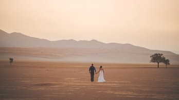 Married heterosexual couple standing in open desert scene with sand dune and trees Wolwedans Namib Rand Namibian Desert Namibia Africa