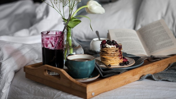 Served breakfast in bed. Pancakes with berries and coffee