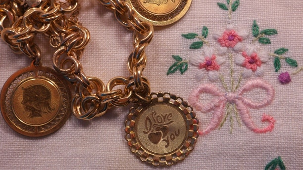 1960s charm bracelet on old embroidered towel, towel embroidered by grandmother circa 1940