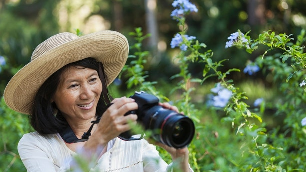 Senior Asian woman (60s) photographing nature.