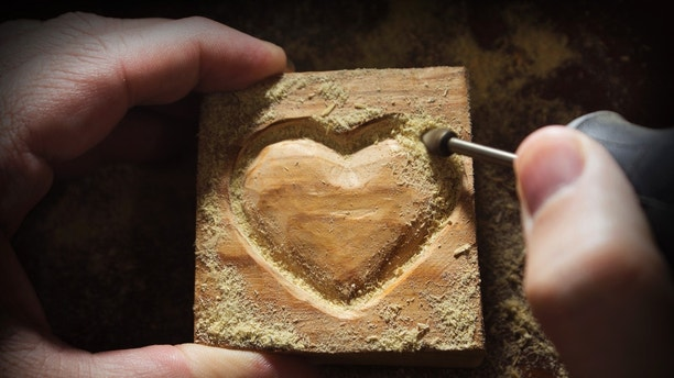 carving wood in heart shape by hand