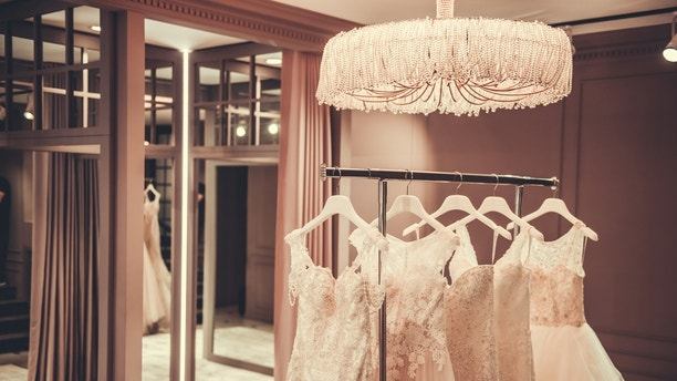 Beautiful tender wedding dresses made of different elegant fabrics on stand in modern wedding salon