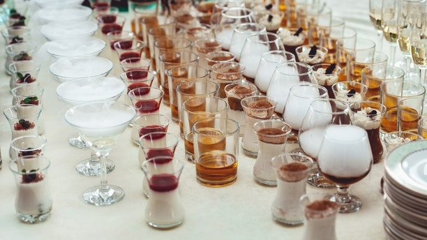 Beautiful row line of different colored alcohol cocktails on a party. Whisky cognac, liquor. Different shapes. dry ice smoke