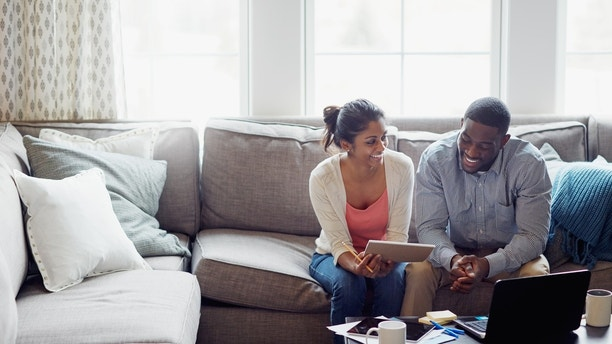 Shot of a young couple going through paperwork together on the sofa at home