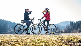 A couple cycling outdoors and taking a break to drink some water
