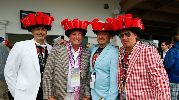 Attendees wear matching elaborate hats before the running of the 139th Kentucky Derby horse race at Churchill Downs in Louisville, Kentucky, May 4, 2013. REUTERS/Jeff Haynes (UNITED STATES  - Tags: SPORT HORSE RACING)   - TB3E95419DY4Z