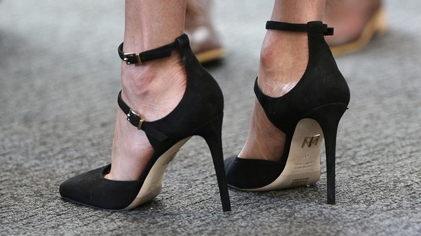 Britain's Prince Harry's fiancee Meghan Markle's shoes are seen as she attends a reception with delegates from the Commonwealth Youth Forum at the Queen Elizabeth II Conference Centre, London, April 18, 2018. Yui Mok/Pool via Reuters - RC13762304D0