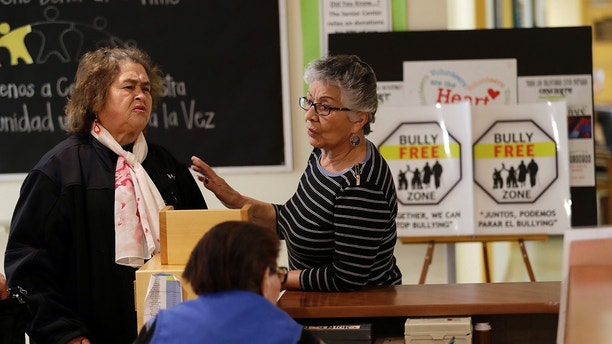 In this Friday, April 13, 2018 photo, two women talk in front of anti-bullying signs at the On Lok 30th Street Senior Center in San Francisco. After problems at the facility, all staff members received 18 hours of training that included lessons on what constitutes bullying, causes of the problem and how to manage such conflicts. Seniors were then invited to similar classes teaching them to alert staff or intervene themselves if they witness bullying. (AP Photo/Marcio Jose Sanchez)