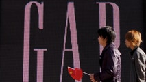 "FILE - In this Nov. 16, 2010 file photo, a man carries a Chinese flag as he walks past U.S. retailer GAP's newly-opened flagship store in Beijing. U.S. clothing retailer Gap has apologized Monday, May 14, 2018, for selling T-shirts with what it says was an ""erroneous"" map of China. (AP Photo/Andy Wong, File)"