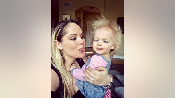 "Taylor McGowan and mum Cara. See SWNS story NYHAIR; A baby girl has been diagnosed with an ultra-rare condition which means her gravity-defying hair is literally impossible to tame. Taylor McGowan, 17 months, is one of just a handful of kids around the world with a known case of Uncombable Hair Syndrome. It causes her bright white hair to stand on end despite efforts by her parents Cara and Tom McGowan - who both have straight brown hair - to brush and style it. The adorable tot attracts crowds wherever she goes and former mental health worker Cara, 32, says she is stopped ""nine or ten times"" on a trip to the shops."