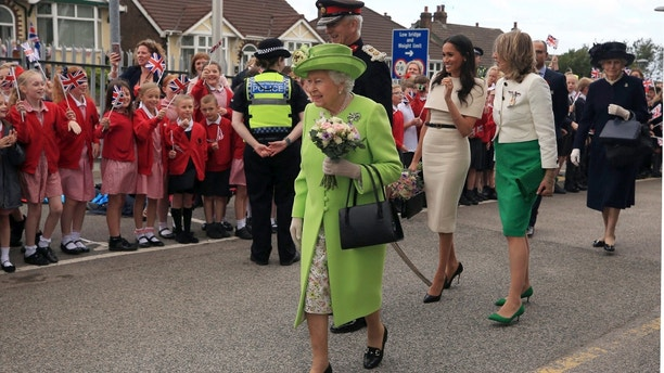 Britain's Queen Elizabeth II and Meghan, the Duchess of Sussex, third right, are welcomed by well-wishers after arriving by Royal Train at Runcorn Station, north west England, Thursday June 14, 2018. (Peter Byrne/Pool via AP)