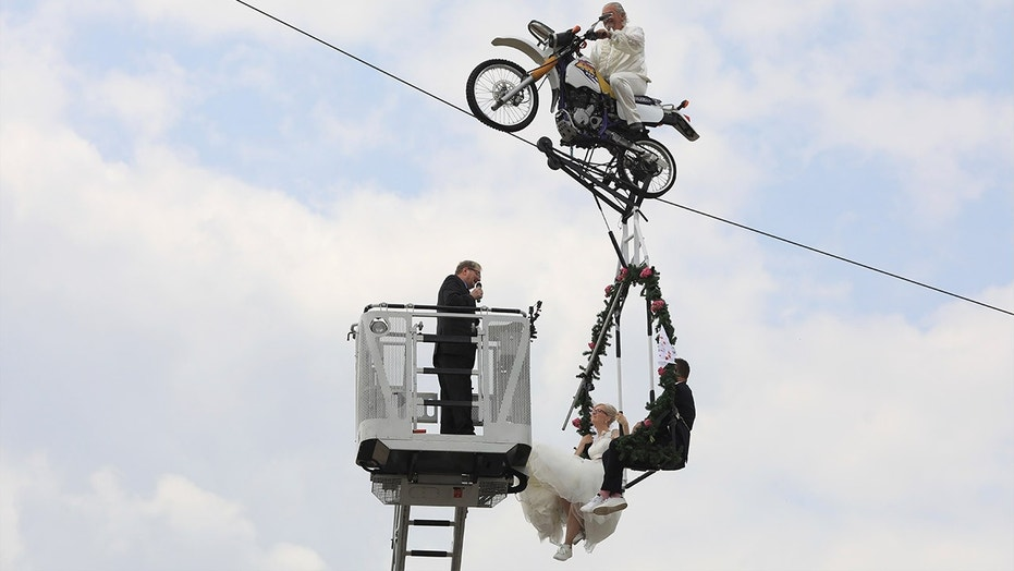 Pastor Stefan Gierung, left, stands in a cage atop of a fire service ladder in front of bride Nicole Backhaus, center, and groom Jens Knorr, right, both sitting in a swing dangling under a motorcycle with artist Falko Traber, top, during the wedding ceremony atop a tightrope in Stassfurt, Germany, Saturday, June 16, 2018.