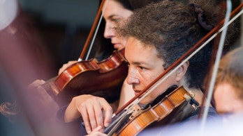 Candid capture of a pair of violinists rehearsing in an orchestral setting.