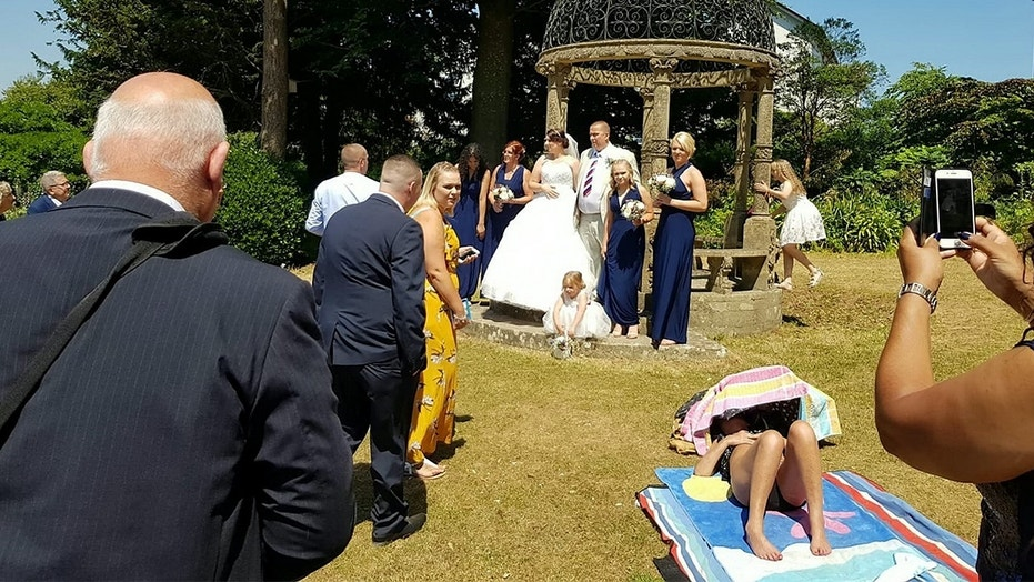 A sunbathing woman allegedly refused to move out a couple's wedding photos.