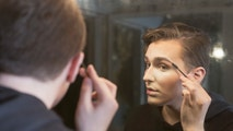 Close-up of a serious young man in a dressing room applying make-up to his face.  He is beginning his transformation into a drag queen. This image is part of a series showing a cross dresser transforming his appearance.