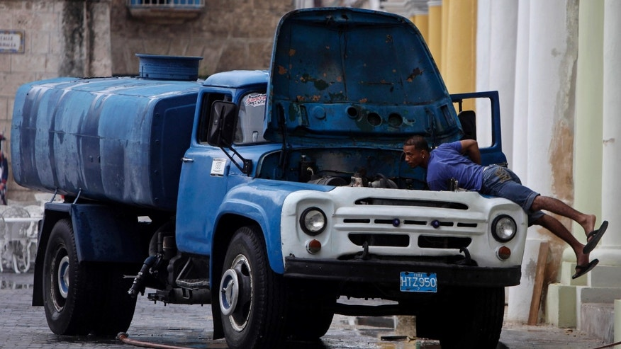 A man checks the engine of his water cistern truck in Old Havana, Cuba, Friday, June 10, 2011. Cuba made official last month it is legalizing the sale of real estate and cars and expanding the ranks of private cooperatives that could serve as engines for the sputtering economy, among other major changes.(AP Photo/Javier Galeano)