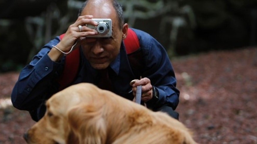 In this photo taken Sept. 7, 2011, Jose Antonio Dominguez places the camera in his forehead as he prepares to take a photograph of his dog at a park in Mexico City Sept. 7, 2011. Dominguez is one of 30 visually impaired or blind people learning photography with the help of the Mexico City foundation Ojos Que Sienten, or Eyes That Feel. (AP Photo/Marco Ugarte)