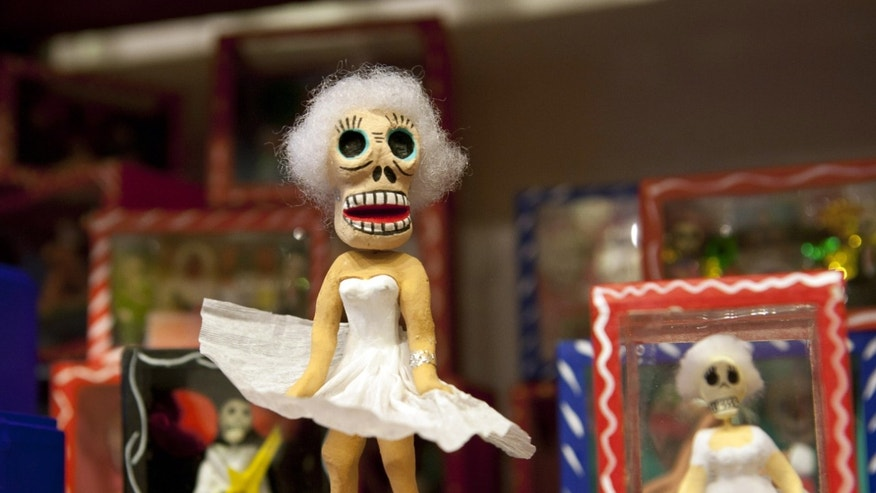 In this Monday, Oct. 3, 2011 photo, a Day of the Dead skeleton figurine designed around a Marilyn Monroe theme stands on a shelf at the store Masks y Mas in Albuquerque, N.M. The shop sells Day of the Dead art and clothing year-round.  (AP Photo/Jake Schoellkopf)