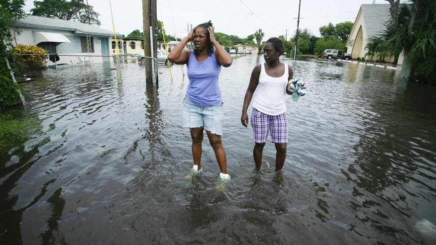Cheryl Wriley reacts as she and Lisa Johnson, right, walk through their Fort Lauderdale, Fla., neighborhood, Monday, Oct. 31, 2011. The Halloween commute won't be a happy one across South Florida following a weekend of heavy rain caused by a stalled tropical weather system. Low-lying areas experienced some flooding early Monday. Broward County health officials warned residents to be careful because floodwaters may contain fecal material, bacteria and viruses. The weather service reports up to 12 inches of rain has fallen in Fort Lauderdale over the past three days. (AP Photo/J Pat Carter)