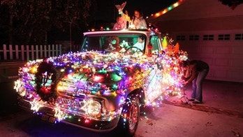"""In this Sunday Dec. 9, 2012 photo, Adriana Leiss and her daughters Gabriella and Amelia replace burned out light bulbs on their 1965 Chevy pick-up truck decorated for Christmas at their house, on what is known as """"Candy Cane Lane"""" in the Woodland Hills section of Los Angeles. (AP Photo/Richard Vogel)"""