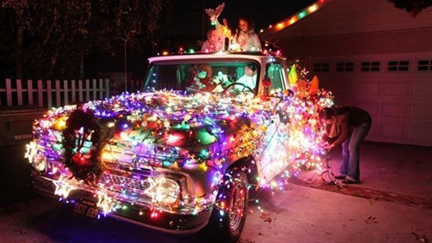"In this Sunday Dec. 9, 2012 photo, Adriana Leiss and her daughters Gabriella and Amelia replace burned out light bulbs on their 1965 Chevy pick-up truck decorated for Christmas at their house, on what is known as ""Candy Cane Lane"" in the Woodland Hills section of Los Angeles. (AP Photo/Richard Vogel)"