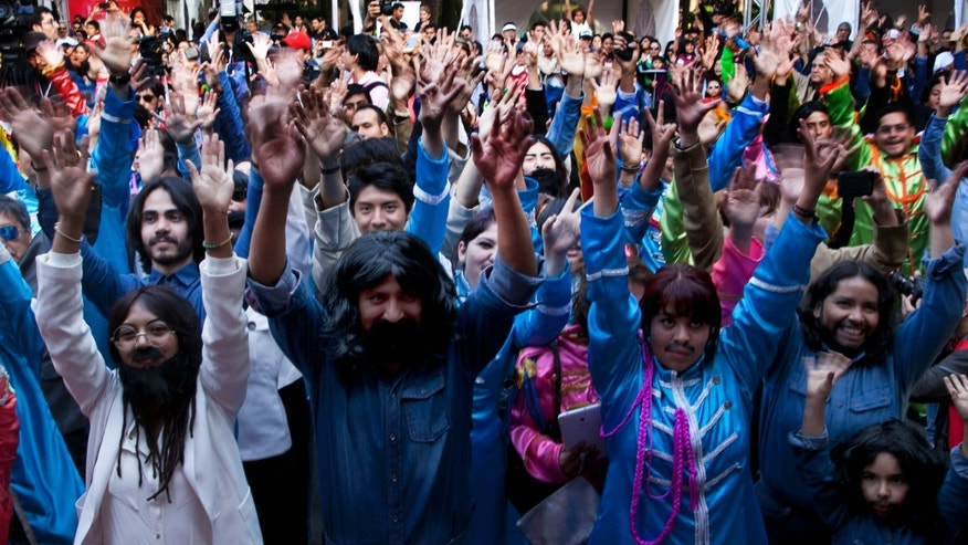 A few hundred people gather in Chapultepec Park in an attempt to set a new Guinness World Record for the highest number of people dressed as The Beatles, in Mexico City, Saturday, Nov. 28, 2015.  (AP Photo/Marco Ugarte)