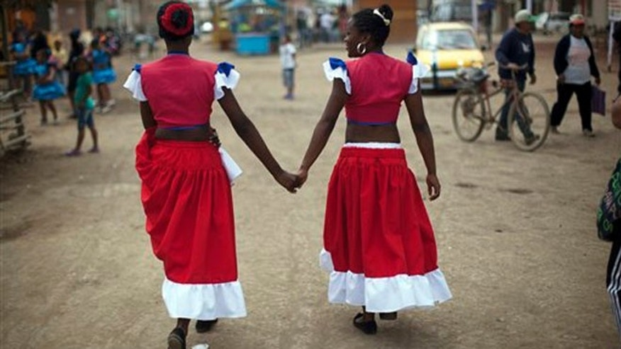In this Sept. 23, 2012 photo, Norma Vargas Portillo, right, and Milagros Gallardo walk hand in hand before performing a traditional Afro-Peruvian dance during festivities in honor of Santa Efigenia in La Quebrada, Peru.  Every year, Peruvians descended from African slaves come to La Quebrada to celebrate the adored black saint Santa Efigenia, the only African saint venerated in Peru. A chapel was built in La Quebrada in the 18th century dedicated to Santa Efigenia, who was popular among the then Spanish colony's African slaves. Cat races, a fireworks dance and a night of eating and drinking close out the celebration.  (AP Photo/Rodrigo Abd)